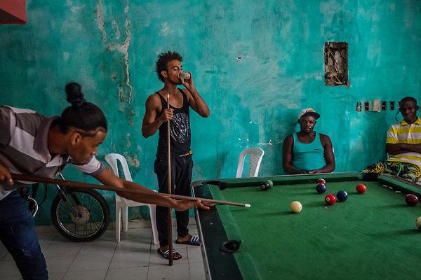 Haitianos y dominicanos juegan billar en el complejo abandonado./ Meridith Kohut para The New York Times