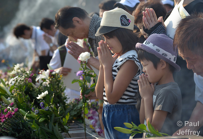People praying on August 6, 2015, at a memorial in Hiroshima, Japan, that commemorates the victims of the atomic bombing of the city by the United States in 1945. (Paul Jeffrey)