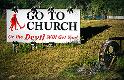 "A roadside sign warns drivers along Alabama Highway I-65 North in Deatsville that they need to to church the avoid the wrath of the Devil. The sign was erected by the late W.S. ""Billy"" Newell in the late 1980's as a way to ""wake up the people,"" Newell told NPR in 2005. Newell briefly changed the sign to, ""We Love Lucy,"" when 2006 gubernatorial candidate Lucy Baxley. Newell died in 2009. (Photo by Carmen K. Sisson/Cloudybright) (Carmen K. Sisson/Cloudybright)"