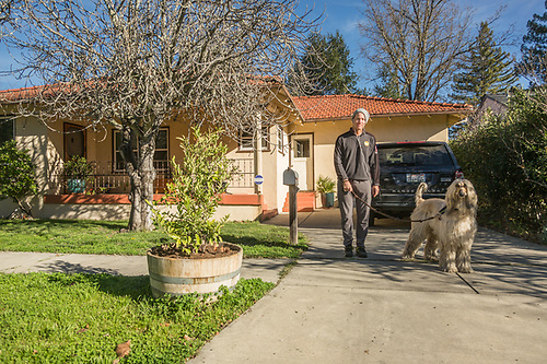 """I should have dressed better...instead of looking like a homeless person.""  -Eric pauses with his dog, Duke,  in front of their home on Myrtle Street in Calistoga. (Clark James Mishler)"