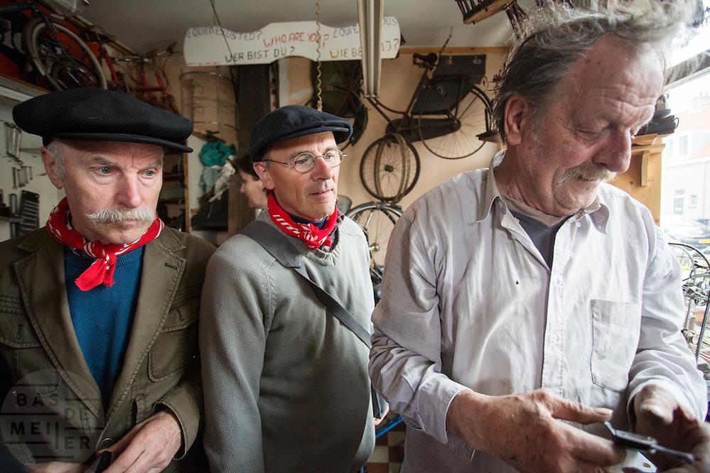 De deelnemers kijken hun ogen uit in de fietsenhandel van Victor (rechts).