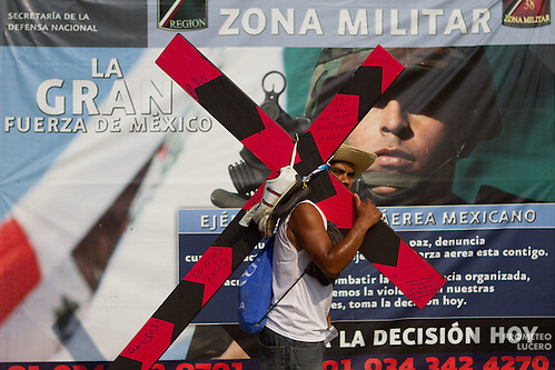 "A central american migrant carries a cross during the ""Viacrucis migrante"" in front of the 38A Military Zone, on April 6th, 2012. (Photo: Prometeo Lucero) (Prometeo Lucero)"