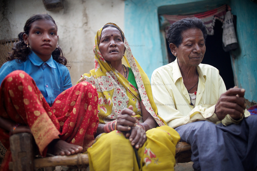 Amar Singh Patel (right) outside the family home with his wife, Sona Bai; and grandaughter, Jaymati (age 11)...Amar Singh Patel, age 60 owns owns 5 acres of land, 1.5 of which is irrigated. He lives in Rathkhandi village, Bilaspur District, Chhattisgarh State with his wife Sona Bai, their daughter and son-in-law and four grandchildren...On this irrigated land, Amar Singh's family cultivate rice using the SRI technique together with a small vegetable plot. The remaining 3.5 acres are leased out to share-croppers. Amar Singh was introduced to SRI by Oxfam partners Jan Swasthya Sahyog (JSS) and began growing rice using this technique in 2007...Amar Singh's land did not always produce enough food for his family to eat. When Amar Singh was a young man, he and his family had to eat wild flowers to survive. They also had to sell their cattle, buy clothing on credit and migrate in search of work...The JSS introduced SRI to Amar Singh and others in his village. SRI is an organic system of intensively growing rice that can double crop yields double. ..Using SRI, Amar Singh and his family produce enough rice for all of their annual needs from only 1.5 acres of land. They now never go hungry...By using SRI Amar Singh never has to spend money on expensive chemicals which degrade the soil. SRI also uses less seed. With fewer inputs Amar Singh has made savings and invested these in his farm. Last year he purchased a new bullock cart. And Amar Singh's grandchildren no longer have to work the land when they should be at school as he did when he was a child. ..The JSS have recruited Amar Singh to advocate for SRI and teach other farmers the benefits of this system of agriculture. ..Photo: Tom Pietrasik.Chhattisgarh, India.November 2012 (Tom Pietrasik)