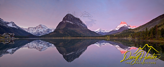 Swiftcurrent Lake sunrise and Panorama. Sunrise at Swiftcurrent Lake in Glacier National Park is a fine place and time  to plant your tripod legs in the morning. Mt. Gould (left) Mt, Grinnell (center) and Mt. Wilbur (right) reaching into the sun cast a nice reflection in the lake as does Swiftcurrent Lodge. (Daryl Hunter's &quot;The Hole Picture&quot;  Daryl L. Hunter has been photographing the Yellowstone Region since 1987, when he packed up his view camera, Pentex 6X7, and his 35mms and headed to Jackson Hole Wyoming. Besides selling photography Daryl also publ)