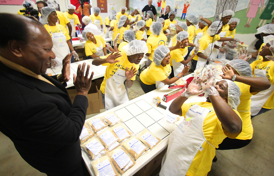 Iowa native and world-renowned opera singer Simon Estes, left, dances and sings with students from the Simon Estes Music High School in Capteown, South Africa, while packaging meals at Meals from the Heartland's West Des Moines warehouse on May 18. (Christopher Gannon/The Register)