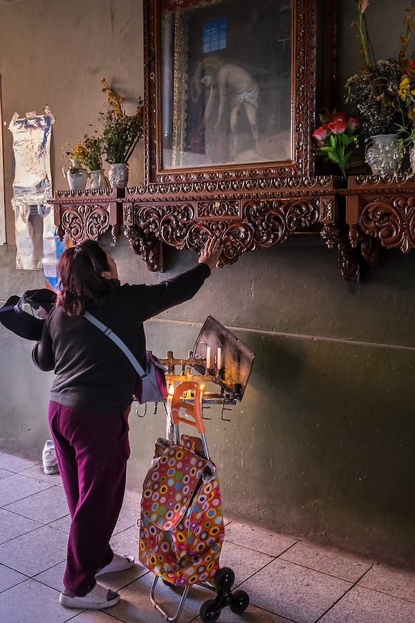 AREQUIPA, PERU - CIRCA APRIL 2014: Peruvian woman worshiping at one the entrances of the San Camilo market in. Arequipa is the Second city of Perú by population with 861,145 inhabitants and is the second most industrialized and commercial city of Peru. (Daniel Korzeniewski)