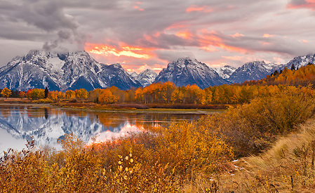 The sun underlights the clouds with pink and orange light during the sunset from Oxbow Bend in Grand Teton National Park. (Benjamin Chase)