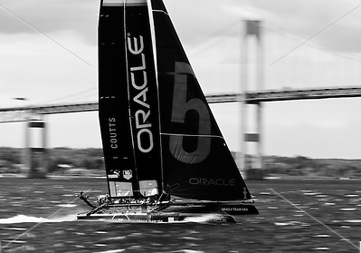 Newport, RI - Russell Coutts on Oracle 5 rips across Narragansett bay in front of the Newport Pell bridge.  The AC45 catamarans were racing during the America's cup world championships held in Newport. (Alexander Nesbitt)