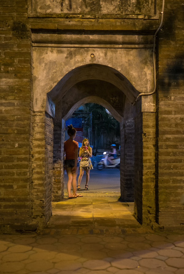 HANOI, VIETNAM - CIRCA SEPTEMBER 2014:  Young Vietnamese women at the Hoan Kiem Lake at night in Hanoi, Vietnam. (Daniel Korzeniewski)