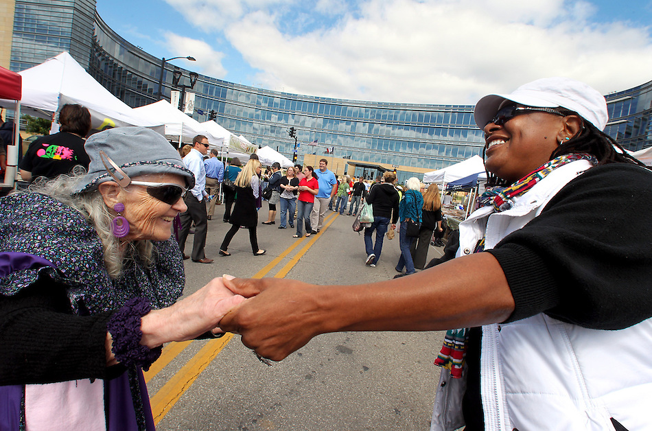 """Nellie west, left, of Altoona, and AJ Singleton of Des Moines enjoy an impromptu Polka dance together during  the midday Downtown Farmers' Market on September 21 in Des Moines.  West, a 75-year-old Polka enthusiast, beckoned the passing Singleton, who happily joined her as music supplied by the Polka Club of Iowa played.  """"I don't know anybody who doesn't smile when they are around Polka music,"""" West said. (Christopher Gannon/The Register)"""