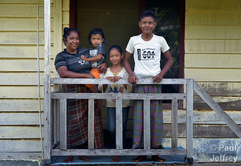 Rusmiati and her children at her home in Lhok Me, in Indonesia's Aceh province. Rusmiati was left homeless by the 2004 tsunami, but YEU, a member of the ACT Alliance, worked with the village to build new houses in a safer area, as well as help revitalize their income generating activities. Her children are Vera, 5, Fathan, 10, and Rahmat, 15. The tsunami killed 221,000 people in Aceh province and left more than 500,000 displaced. This image compares to a similar image taken of Rusmiati in the same spot in 2007, with her two older children. (Paul Jeffrey)