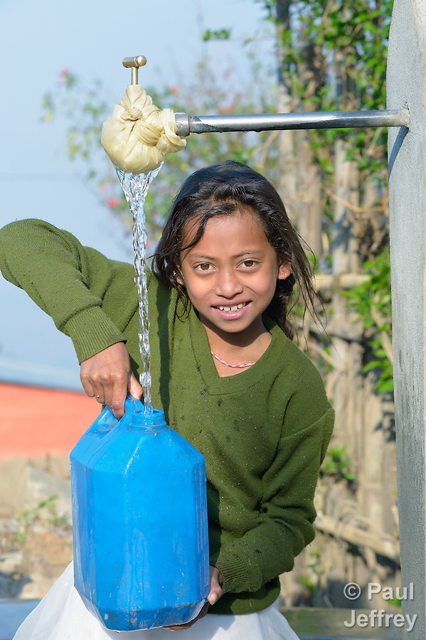 A girl fills a container with water at a community spigot in Makaising, a village in the Gorkha District of Nepal that was hard hit by a devastating 2015 earthquake. (Paul Jeffrey)