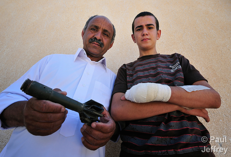 In Misrata, Libya, Abdul Majeed (left), holds the remains of a rifle grenade that landed near his family's home but didn't explode. His 15-year old son Mohammed (right) found the mortar and while playing with it the next day, April 1, lost part of his left hand when it exploded. He has since had three operations on his arm. A team from the ACT Alliance is in Misrata to help dispose of unexploded ordnance which continues to threaten the civilian population.