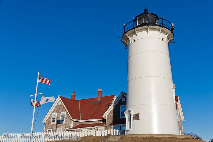 "Nobska Lighthouse in Woods Hole, MA on Cape Cod.  The red-roofed keeper's house and white and black lighthouse are both visible, as the wind blows the flags in front of a clear blue sky. I love how the lighthouse feels like it standing proud; a little bit of Americana.  This image is cropped to be printed at 12x18"". (Marc Perkins)"