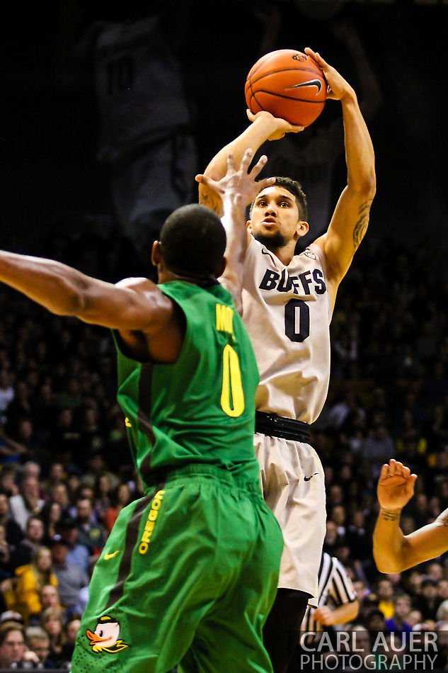 January 5th, 2014:  Colorado Buffaloes junior guard Askia Booker (0) rises up for a shot over Oregon Ducks redshirt senior forward Mike Moser (0) in the second half of the NCAA Basketball game between the Oregon Ducks and the University of Colorado Buffaloes at the Coors Events Center in Boulder, Colorado (Carl Auer/ZUMAPRESS.com)
