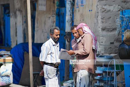 SANAA, YEMEN - SEPTEMBER 16, 2006: Unidentified men read newspaper at the street in Sanaa, Yemen. (Dmitry Chulov)