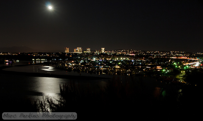 A moonlit view of Lower Newport Bay (and partially Upper Newport Bay) with PCH (Pacific Coast Highway) to the right and Newport Center's many tall buildings that surround Fashion Island in Newport Beach, CA.  Saddleback Mountain (Santiago Peak and Modjeska Peak) can be seen off in the distance, to the left.  This image is a minimally manipulated single-frame, long-exposure capture. (Marc Perkins/Marc Perkins Photography)