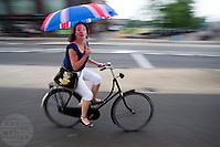 Een vrouw fietst met een paraplu met de Engelse vlag door een zomerse regenbui. A woman is cycling with an umbrella in the rain. (Bas de Meijer)