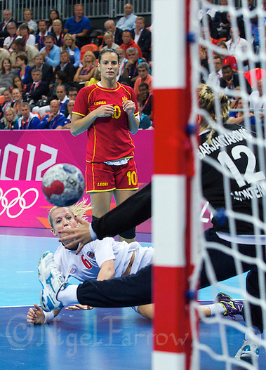 11 AUG 2012 - LONDON, GBR - Heidi Løke (NOR) (bottom left) of Norway watches the ball after shooting during the women's London 2012 Olympic Games handball final against Montenegro at the Basketball Arena in the Olympic Park, in Stratford, London, Great Britain (PHOTO (C) 2012 NIGEL FARROW) (NIGEL FARROW/(C) 2012 NIGEL FARROW)