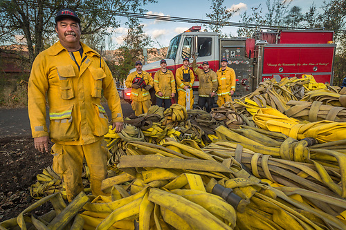 """These hoses will be cleaned, tested and put back into service.""  -Captain Rutledge, of the Bakersfield City Fire Department (left), works with his crew and a crew from the City of Clovis Fire Department to bundle up hundreds of feet of fire hose used while battling the Tubbs fire along Hwy. 128 near Bennett Lane, north of Calistoga. (Clark James Mishler)"