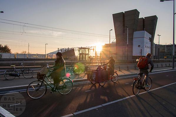 In Amsterdam fietsen mensen, waaronder een vrouw met kinderen in de bakfiets, over een brug bij de Prins Hendrikkade. In Amsterdam cyclist, amongst others a woman with her children on a cargo bike, ride over a bridge near the Prins Hendrikkade. (Bas de Meijer)