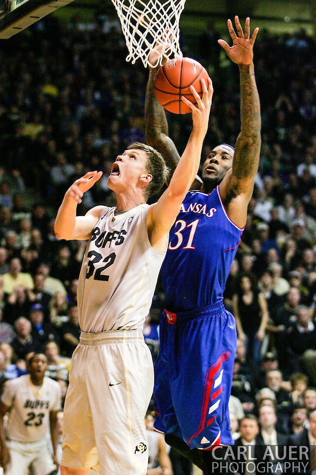 December 7th, 2013:  Colorado Buffaloes senior center Ben Mills (32) attempts to shoot past Kansas Jayhawks redshirt sophomore forward Jamari Traylor (31) during the second half of the NCAA Basketball game between the Kansas Jayhawks and the University of Colorado Buffaloes at the Coors Events Center in Boulder, Colorado (Carl Auer/ZUMAPRESS.com)