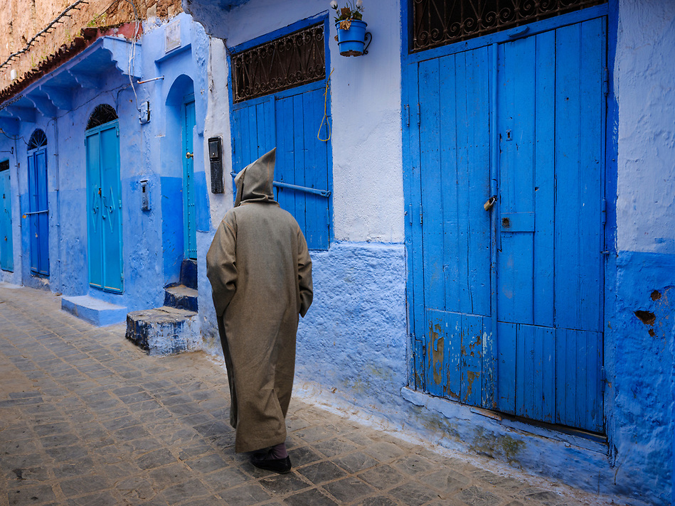 CHEFCHAOUEN, MOROCCO - CIRCA APRIL 2017: Moroccan man walking in the streets of Chefchaouen wearing a traditional djellaba (Daniel Korzeniewski)
