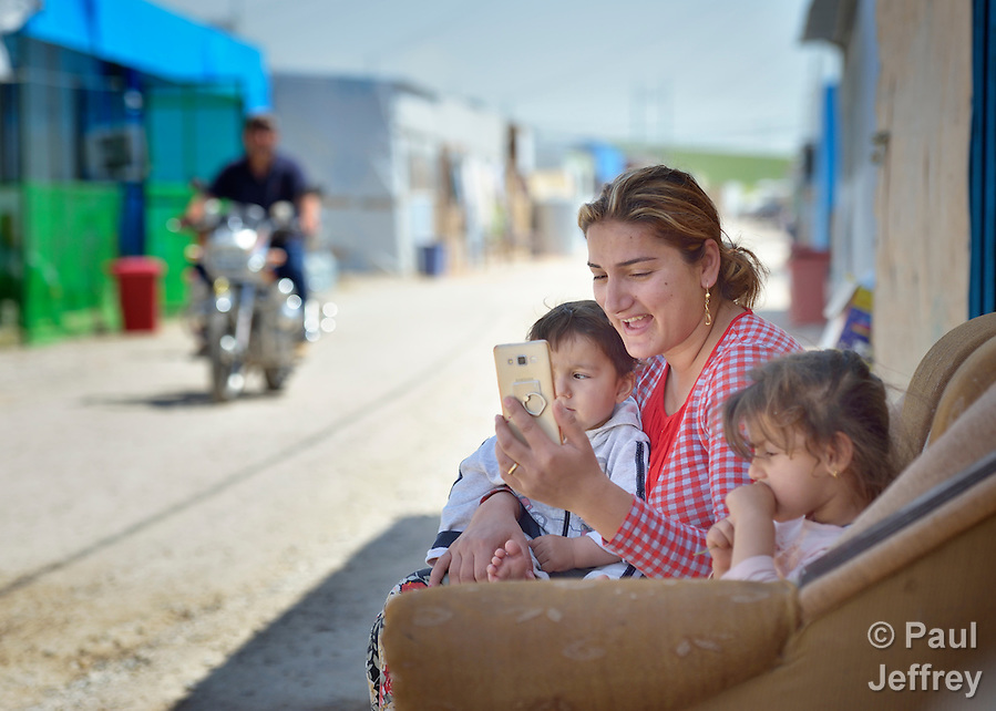 Adra Samar uses Skype to talk to a relative in Baghdad as she sits in a camp for internally displaced families in Ankawa, near Erbil, Iraq, on April 8, 2016. Residents of the camp, mostly Christians, were displaced from Mosul, Qaraqosh and other communities in Iraq when ISIS swept through the area in 2014. (Paul Jeffrey)