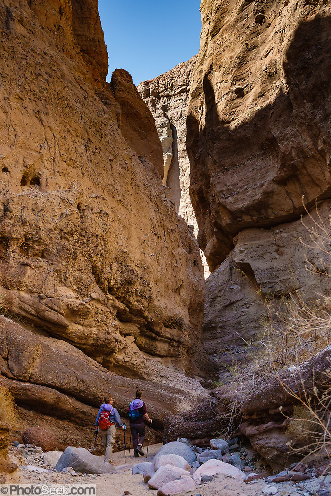 Hikers descend into a slot along the Ladder Canyon and Painted Canyon Loop Trail, Mecca Hills Wilderness, managed by BLM's Palm Springs-South Coast Field Office, near Mecca, California, USA. (© Tom Dempsey / PhotoSeek.com)