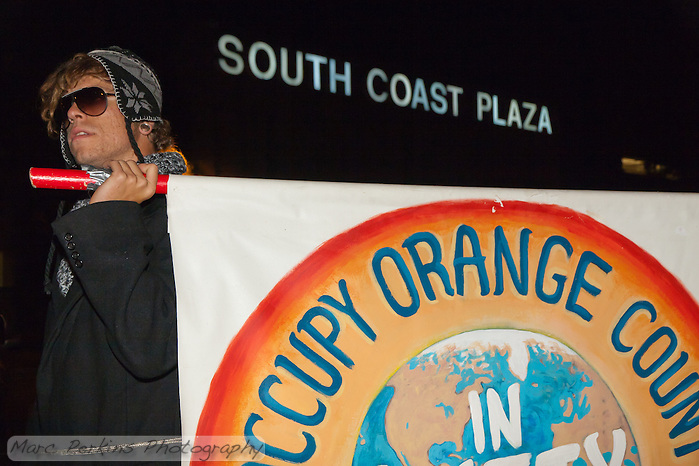 An unknown marcher holds the Occupy Orange County sign while marching at South Coast Plaza early in the morning (1:08am)  on Black Friday.  A lit South Coast Plaza sign is lit in the background.   The protesters were tied together by rope, being led by a single protestor dressed in a suit (as a banker), symbolizing how the 1% lead the 99%. (Marc C. Perkins)