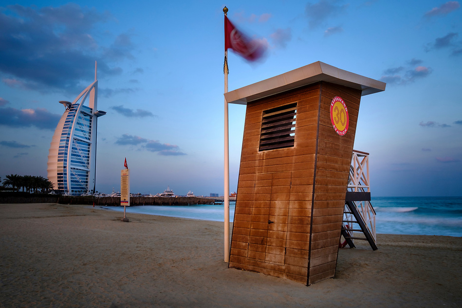 UNITED ARAB EMIRATES, DUBAI - CIRCA JANUARY 2017: Lifeguard station at the Jumeirah Public Beach at sunrise. with view of the Burj Al Arab, the only 7 star hotel in the world. (Daniel Korzeniewski)