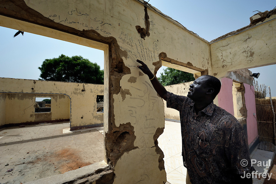 Kuol Deng Kuol, the paramount chief of the Dinka Ngok, looks at racist graffiti written on the walls of looted government offices in Abyei, a town at the center of the contested Abyei region along the border between Sudan and South Sudan. The town was looted and burned in 2011 when mostly Arab soldiers and militias from the northern Republic of Sudan swept through the area, chasing out more than 100,000 Dinka Ngok residents. The chief and a few thousand other families returned once northern combatants withdrew in 2012. On May 4, 2013, the chief was killed when his vehicle, part of a United Nations convoy, was fired upon by Khartoum-backed Misseriya militia. (Paul Jeffrey)