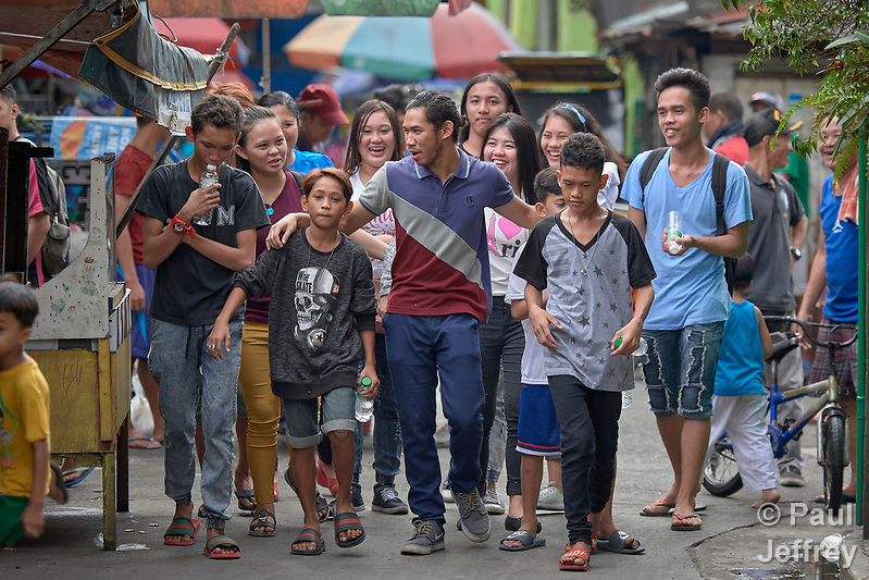 "Larren Jo ""LJ"" Bacilio, a teacher in the Alternative Learning System of the Kapatiran-Kaunlaran Foundation (KKFI), walks with some of his students in the Tondo neighborhood of Manila, Philippines. KKFI is supported by United Methodist Women. (Paul Jeffrey)"