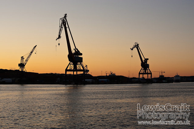 Silhouetted cranes at the docks on the Gota alv river, Gothenburg, Sweden (Lewis Craik)