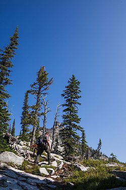 A solitary man carries a hip-mounted pistol and hand-carried shotgun for protection while hiking in North Idaho to Harrison Peak of the Selkirk Range. (Benjamin Chase)