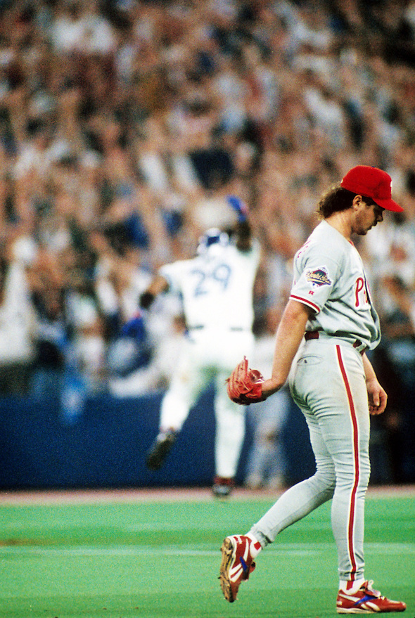 TORONTO, ONTARIO, CANADA - OCTOBER 23: Pitcher Mitch Williams of the Philadelphia Phillies walks off the field as Joe Carter of the Toronto Blue Jays jumps for joy in the background after Carter hit a World Series winning walk off home run in Game Six of the 1993 World Series at the Skydome on October 23,1993 in Toronto, Ontario, Canada. The Blue Jays won the game 8-6, winning the Series 4-2.  (Photo by Ron Vesely) (Ron Vesely)