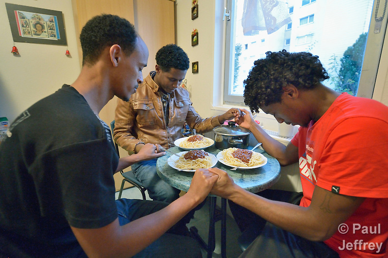 Eritrean asylum seekers pray before eating in their room in a church-run shelter in Freudenstadt, Germany. The Freundesdreis Asyl is run by Christlicher Kirchen, and managed by a retired United Methodist pastor. The shelter has 18 asylum seekers from Eritrea and 10 from Gambia. They came to Europe via Sudan and Libya, crossing the Mediterranean to Italy. (Paul Jeffrey)