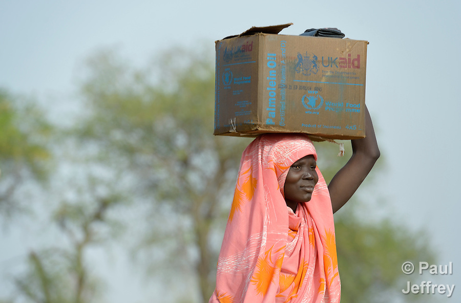 A displaced woman walks home after receiving emergency food supplies from the United Nations World Food Program in Agok, a town in the contested Abyei region where tens of thousands of people fled in 2011 after an attack by soldiers and militias from the northern Republic of Sudan on most parts of Abyei. Although the 2005 Comprehensive Peace Agreement called for residents of Abyei--which sits on the border between Sudan and South Sudan--to hold a referendum on whether they wanted to align with the north or the newly independent South Sudan, the government in Khartoum and northern-backed Misseriya nomads, excluded from voting as they only live part of the year in Abyei, blocked the vote and attacked the majority Dinka Ngok population. The African Union has proposed a new peace plan, including a referendum to be held in October 2013, but it has been rejected by the Misseriya and Khartoum. The Catholic parish of Abyei, with support from Caritas South Sudan and other international church partners, has maintained its pastoral presence among the displaced and assisted them with food, shelter, and other relief supplies. (Paul Jeffrey)