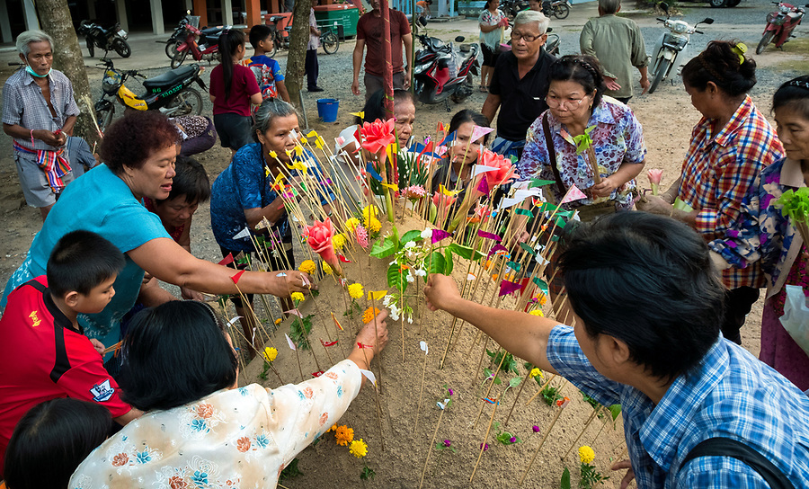 Members of the congregation place prayer flags on a sand stupa as part of Songkran festivities in Nakhon Nayok, Thailand, April 18, 2017. (Lee Craker/Lee Craker, Photographer)
