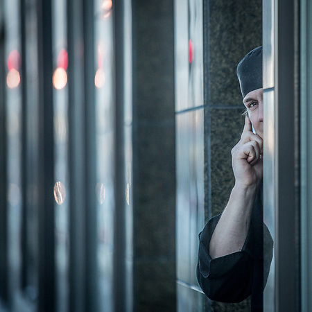 Hilton worker makes a personal phone call while on break in downtown Anchorage (Clark James Mishler)