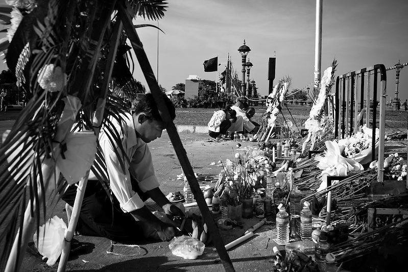 Mourners gather at the base of the bridge where two nights prior several hundred people lost their lives in a stampede tragedy. An unkown event sparked panic and thousands attempted to flee Diamond Island in the middle of the Mekong River over the bridge connecting it to the river bank. (Quinn Ryan Mattingly)