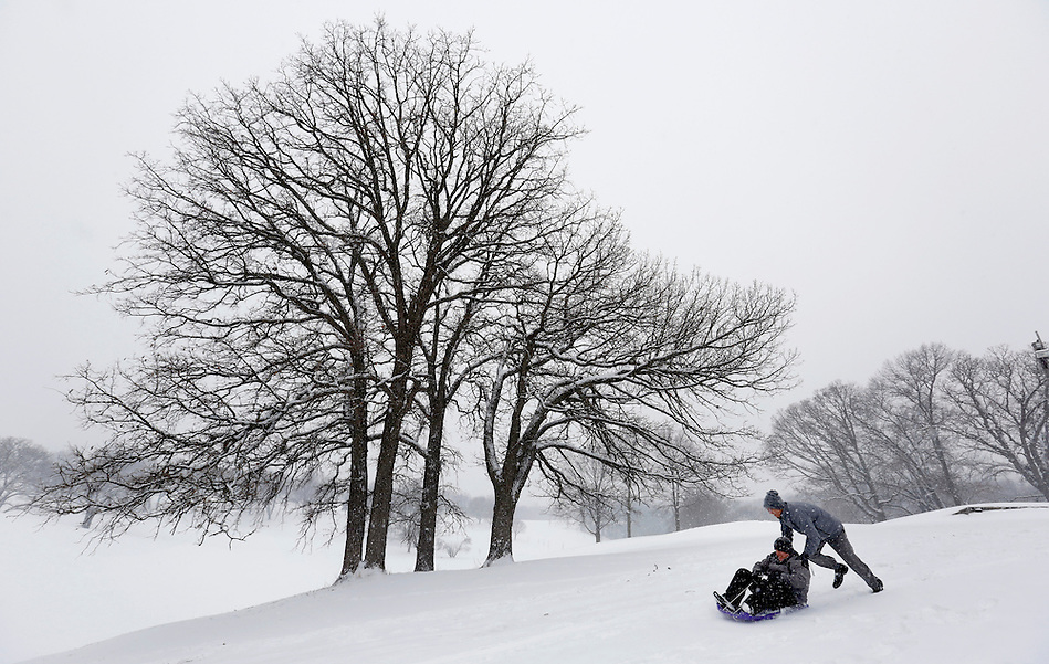 Casey Baney pushes friend Casey Downing on a toboggan to give him a start at the top of a hill while sledding with friends Tuesday, February 4, 2014 at Waveland Golf Course in Des Moines.  Both men, from Des Moines, left work early to have some fun in the snow. (Christopher Gannon/The Register)