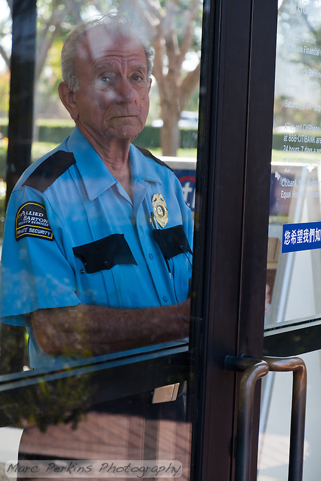 Charles, a security guard at a Citibank branch in Irvine, CA, warily watches through a locked door as protesters from the Occupy Orange County, Irvine camp march in front of his bank on November 5. (Marc C. Perkins)