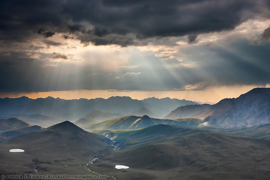 Aerial of dramatic clouds spilling light over the philip smith mountains in the Arctic National Wildlife Refuge, Brooks Range mountains, Alaska. (Patrick J Endres / AlaskaPhotoGraphics.com)