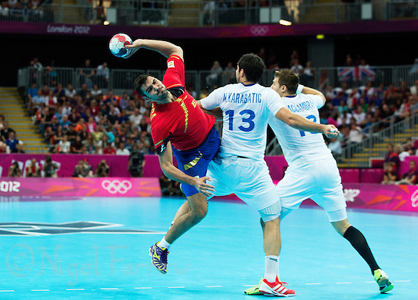 08 AUG 2012 - LONDON, GBR - Jorge Maqueda Pena (ESP) of Spain (left) dives past Nikola Karabatic (FRA) (centre) and William Accambray (FRA) of France (right) to shoot during their men's London 2012 Olympic Games quarter final match at the Basketball Arena in the Olympic Park, in Stratford, London, Great Britain .(PHOTO (C) 2012 NIGEL FARROW) (NIGEL FARROW/(C) 2012 NIGEL FARROW)