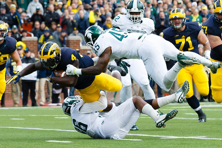 Oct 17, 2015; Ann Arbor, MI, USA; Michigan Wolverines running back De'Veon Smith (4) is tackled by Michigan State Spartans linebacker Darien Harris (45) in the first half at Michigan Stadium. Mandatory Credit: Rick Osentoski-USA TODAY Sports (Rick Osentoski/Rick Osentoski-USA TODAY Sports)