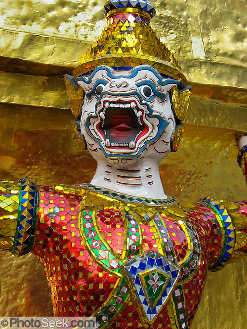 "Asia Contemporary: A demon guards at the bottom of a gilded chedi (or stupa), at the Temple of the Emerald Buddha (Wat Phra Kaew), which is a shining complex of buildings within the grounds of the Grand Palace in Bangkok, Thailand. The Grand Palace (or Phra Borom Maha Ratcha Wang, in Thai) in Bangkok, Thailand, was built on the east bank of the Chao Phraya River starting in 1782, during the reign of Rama I. It served as the official residence of the king of Thailand from the 18th century to the mid-20th century. Photo by Carol Dempsey. Published in ""Light Travel: Photography on the Go"" by Tom Dempsey 2009, 2010. (© Carol Dempsey / Photoseek.com)"