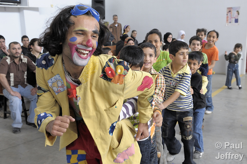 Rahman Aidi Mashoof, a member of the Happy Family Team for Childhood Peace, helps Iraqi refugee children have fun while they and their families wait to be registered at an intake center of the United Nations High Commissioner for Refugees in Douma, on the outskirts of Damascus, Syria. More than one million Iraqi refugees may reside in Syria, and the UN provides assistance with education, food, housing, and a variety of other services. The Happy Family Team has three members, all Iraqi refugees themselves. (Paul Jeffrey)