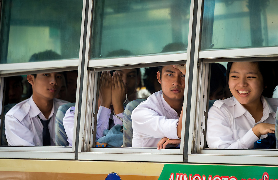 YANGON, MYANMAR - CIRCA DECEMBER 2013: Passengers looking through a bus window in a busy street in Yangon. (Daniel Korzeniewski)
