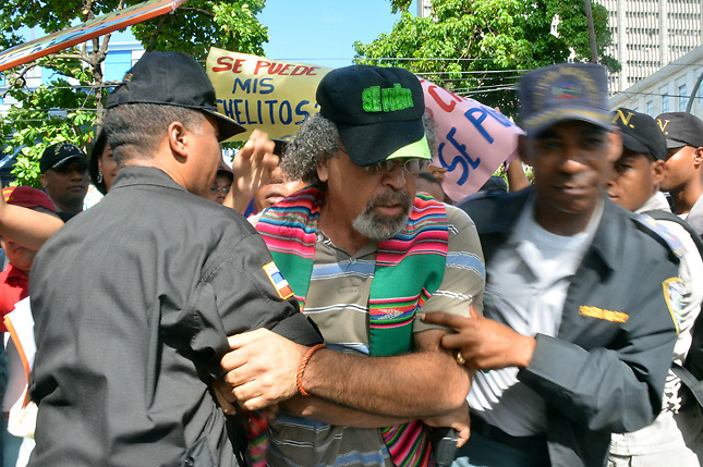 El padre Rogelio Cruz, apresado por dos agentes policiales durante una protesta por la preservación de Loma Miranda.